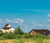 Einige Häuser, im Hintergrund Windkraftanlagen