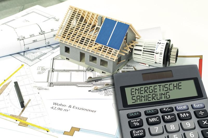 Konstuktionszeichnungen von Gebäuden, darauf das Modell eines Hauses und ein Taschenrechner
