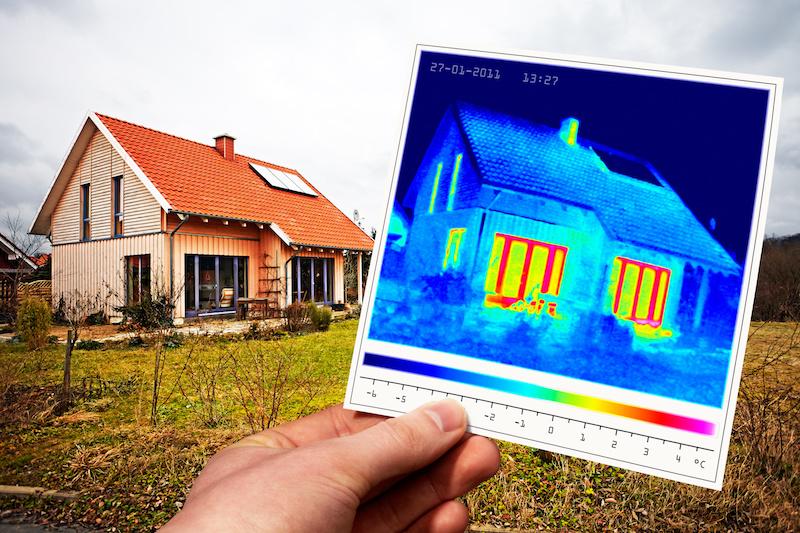 Im Hintergrund ein Einfamilienhaus, im Vordergrund eine Hand, die eine Thermografieaufnahme hält