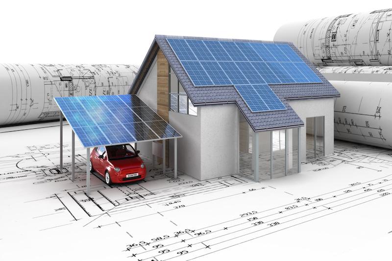 Modell eines Hauses mit PV-Modulen auf und vor Architektur-Plänen
