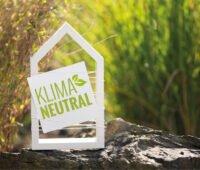Weißes Haus vor natürlichen Hintergrund mit Schild Klimaneutral