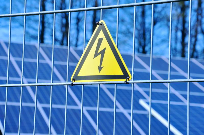 Solarmodule hinter einem Zaun. Am Zaun ein Warnzeichen.