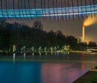 Nachstimmung im Oberhausen. Am oberen Bildrand eine beleuchtete Brücke über einem Kanal. Weiter hinten ein beleuchteter Schornstein.
