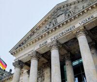 """Das Eingangsportal des Deutschen Bundestags von schräg unten betrachtet mit der Inschrift im Stein oben: """"Dem deutschen Volke"""", die bundesdeutsche Flagge links im Bild"""