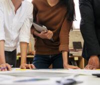 Menschen beugen sich über einen Plan auf einem Tisch - Symbolbild für kommunale Wärmeplanung, Planung