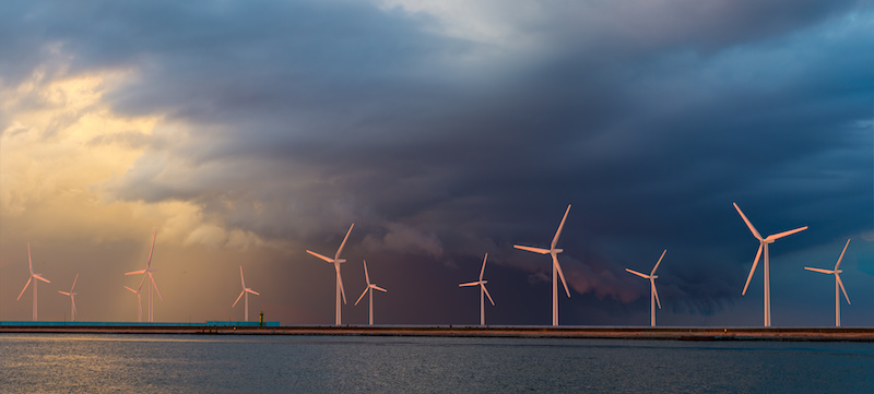 Offshore-Windkraft: Windkraftanlagen auf dem Meer vor dunklen Wolken