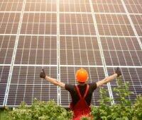 Ein Arbeiter mit orangem Helm und roter Latzhose steht vor Photovoltaikmodulen, streckt die Arme auseinander und zeit mit en Daumen nach oben.