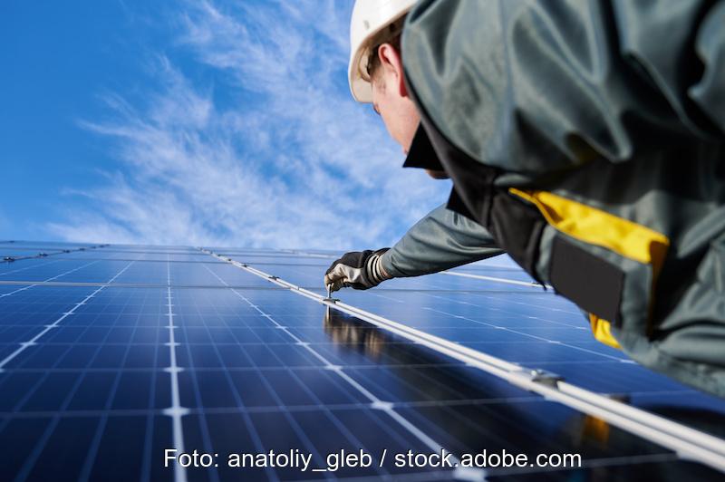 Solarinstallateur rechts vor Solarmodulen, die in die Höhe ragen.