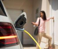 im Vordergrund ein Elektrofahrzeug, an das ein Ladekabel angeschlossen ist. Im Hintergrund eine Frau, die eine Haustür öffnet.