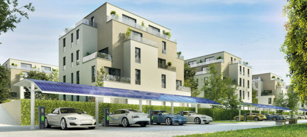 Im Hintergrund ein Mehrfamilienhaus, vorn Elektrofahrzeuge mit Ladestationen, die unter einem Carport mit Photovoltaikmodulen stehen.