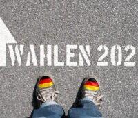"""Straßenbelag, auf den """"Wahlen 2021"""" geschrieben wurde. Davor unten im Bild ein paar Schuhe. Bald ist Wahlkampf."""