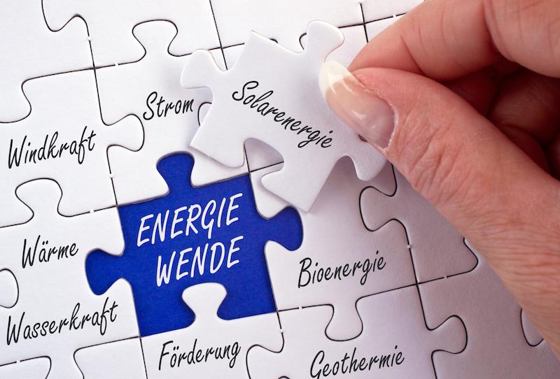 Puzzlespiel zur Energiewende. Das Teil zur Solarenergie wird in einer Hand gehalten