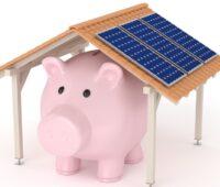 Sparschwein unter einem Dach mit Photovoltaik-Modulen