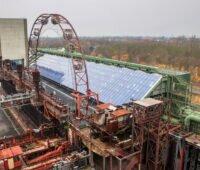 In der Mitte des Bildes eine große PV-Anlage. Sie befindet sich auf einer Industrieanlage der Zeche Zollverein.