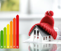 Links eine Grafik mit der Effizienzskala ab A, rechts das Modell eines Hauses unter einer Pudelmütze - Illustration Gebäudeenergiegesetz