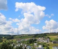 Im Vordergrund ein Dort im Hunsrück, im Hintergrund Windkraftanlagen mit akzeptierten Windkraft-Abständen