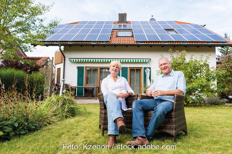 Ein Paar sitzt im Garten vor einem Einfamilienhaus mit Photovoltaikanlage auf dem Dach.