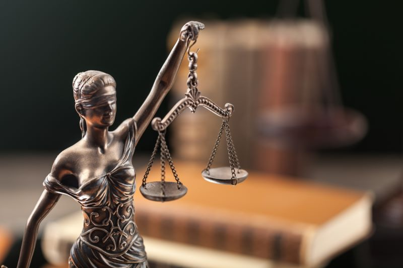 Justitita mit der Waage vor Gesetzbüchern.