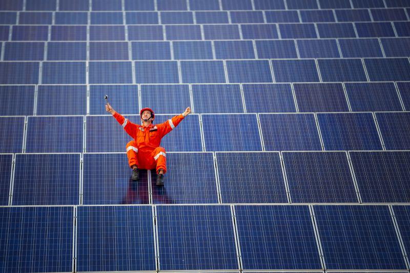 Inmitten eines Feldes von Solarmodulen freut sich ein MOnteur mit erhobenen Armen