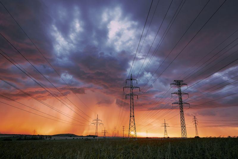 Dunkle Wolken über Stromtrassen