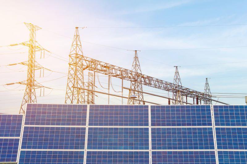 Im Vordergrund Solarmodule vor Strommasten und sonnig blauem Himmel.