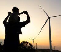 Vater mit Kind im Gegenlöicht vor Windenergieanlagen bei Sonnenaufgang