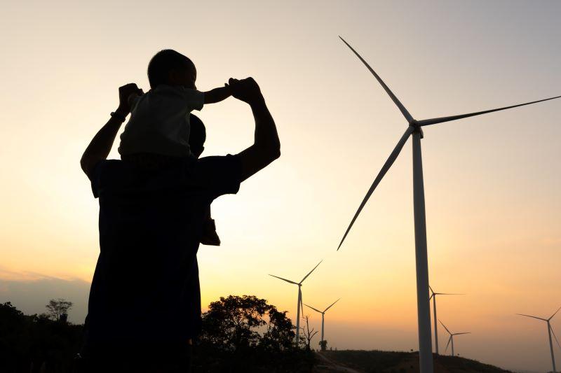Vater mit Kind im Gegenlicht vor Windenergieanlagen bei Sonnenaufgang