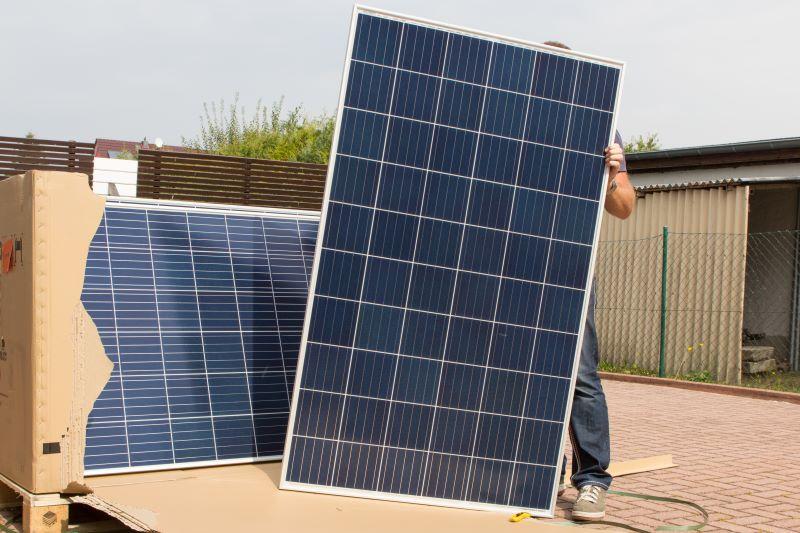 Ein Mann hinter einem Solarmodul, das aus einem verpackten Paket stammt.
