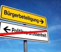 Die Montage zeigt zwei Straßenschilder. Eines zeigt in Richtung Bürgerbeteiligung, das andere in die Gegenrichtung. Darauf steht Politikverdrossenheit. Das Wort ist durchgestrichen.