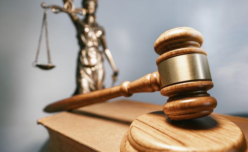 Ein Richterstock im Vordergrund. Im Hintergrund Justitia mit der Waage.