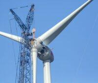 Propeller wird per Kran an eine große Windkraftanlage gehoben