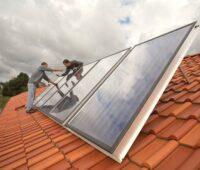Handwerker mit Handschlag nach beendeter Installation von Solarkollektoren.