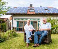 Älteres Paar vor Einfamilienhaus mit Photovoltaik-Anlage