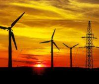 Windanlagen und Strommasten vor buntem Abendhimmel und untergehender Sonne.