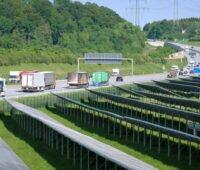 Vordergrund: PV-Freiflächenanlage, Hingtergrund: Autobahn