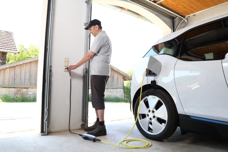 Ein Mann lädt sein E-Auto in der Garage.