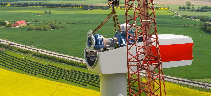 Eine Windgondel bei der Montage hoch über Feldern.