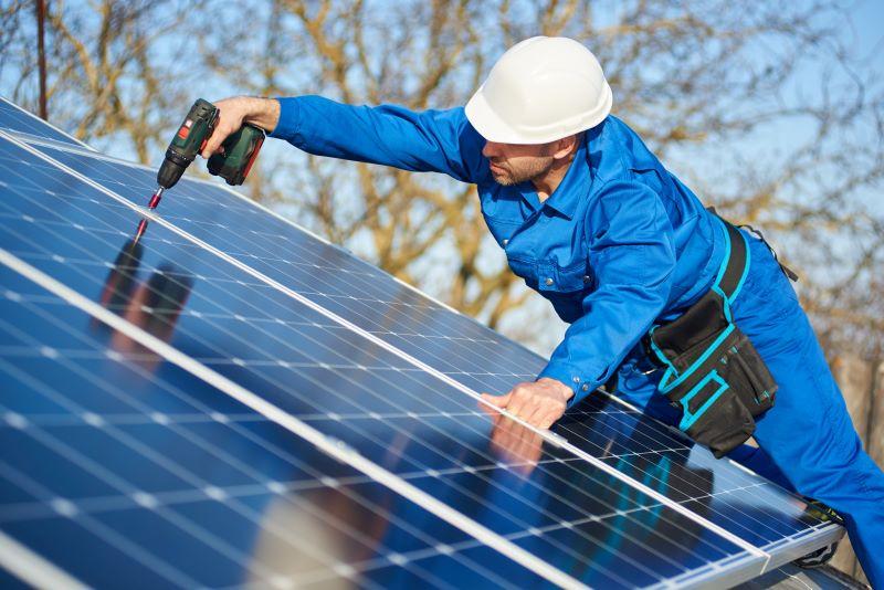 Ein Arbeiter im Blaumann montiert Solarmodule.