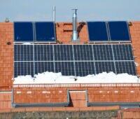 Rotes Ziegeldach mit Solarthermiekollektoren und Photovoltaikmodulen