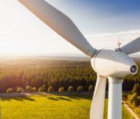 Ein Windkraftturbine im Gegenlicht über Feldern.