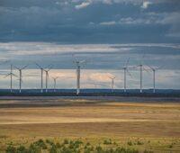 Ein Windpark vor karger Fläche und unter bewegtem Himmel