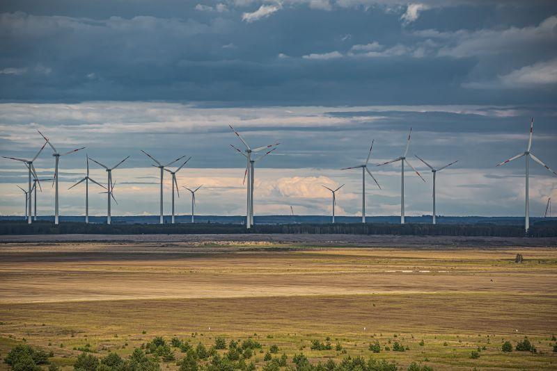 Windräder in flacher Landschaft auf braunem Boden vor Wolken.