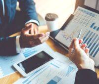 Businesshände und ein Laptop mit Finanzzahlen.