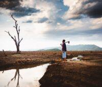 Ein asiatischer landwirt blickt auf vertrockneten Baum und Land mit wenig Wasser.