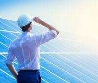 Mann mit Hemd und Helm blickt an einer PV-Anlage in die Sonne.