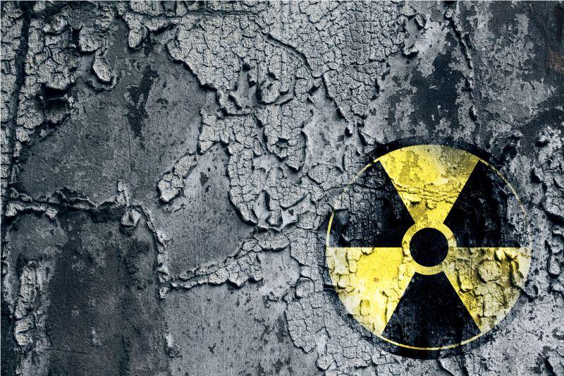 Das Zeichen für gefährliche Atomkraft auf schwarzem verwitterten Hintergrund.