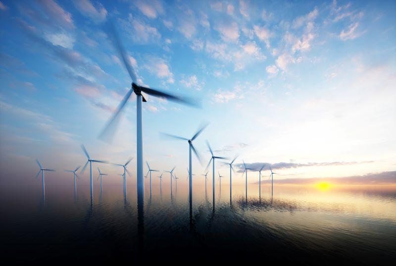 Ein Windpark auf See bei Sonnenaufgang.