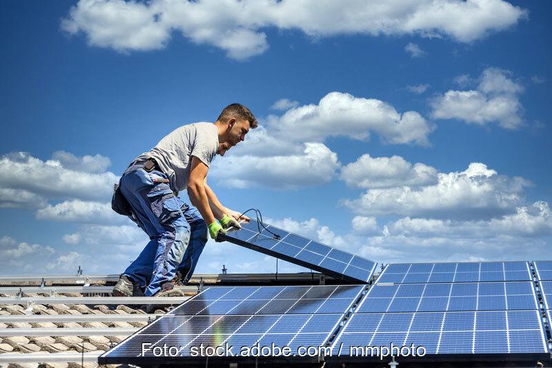 Zwei Monteure verlegen Solarmodule auf Schrägdach