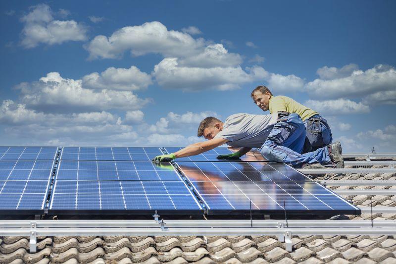 Zwei Monteure installieren eine PV-Anlage auf dem Dach.