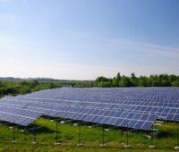 Eine PV-Freiflächenanlagen auf grüner Wiese unter blauem Himmel